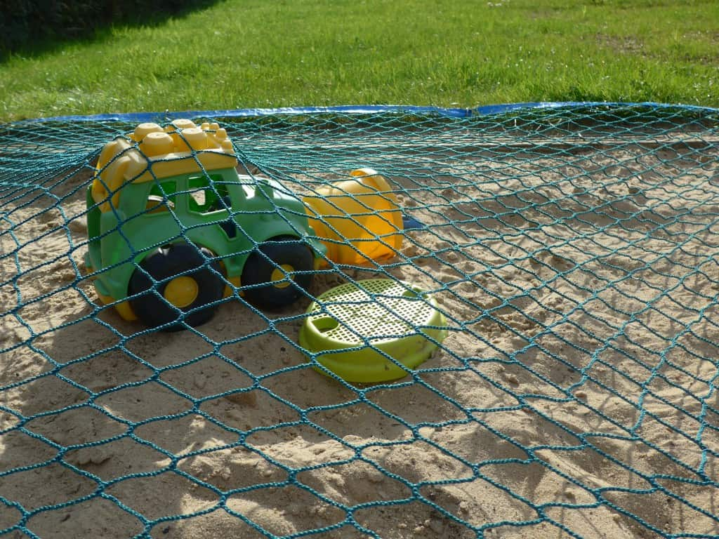Sandkastennetz deckt Spielzeug im Sandkasten ab.
