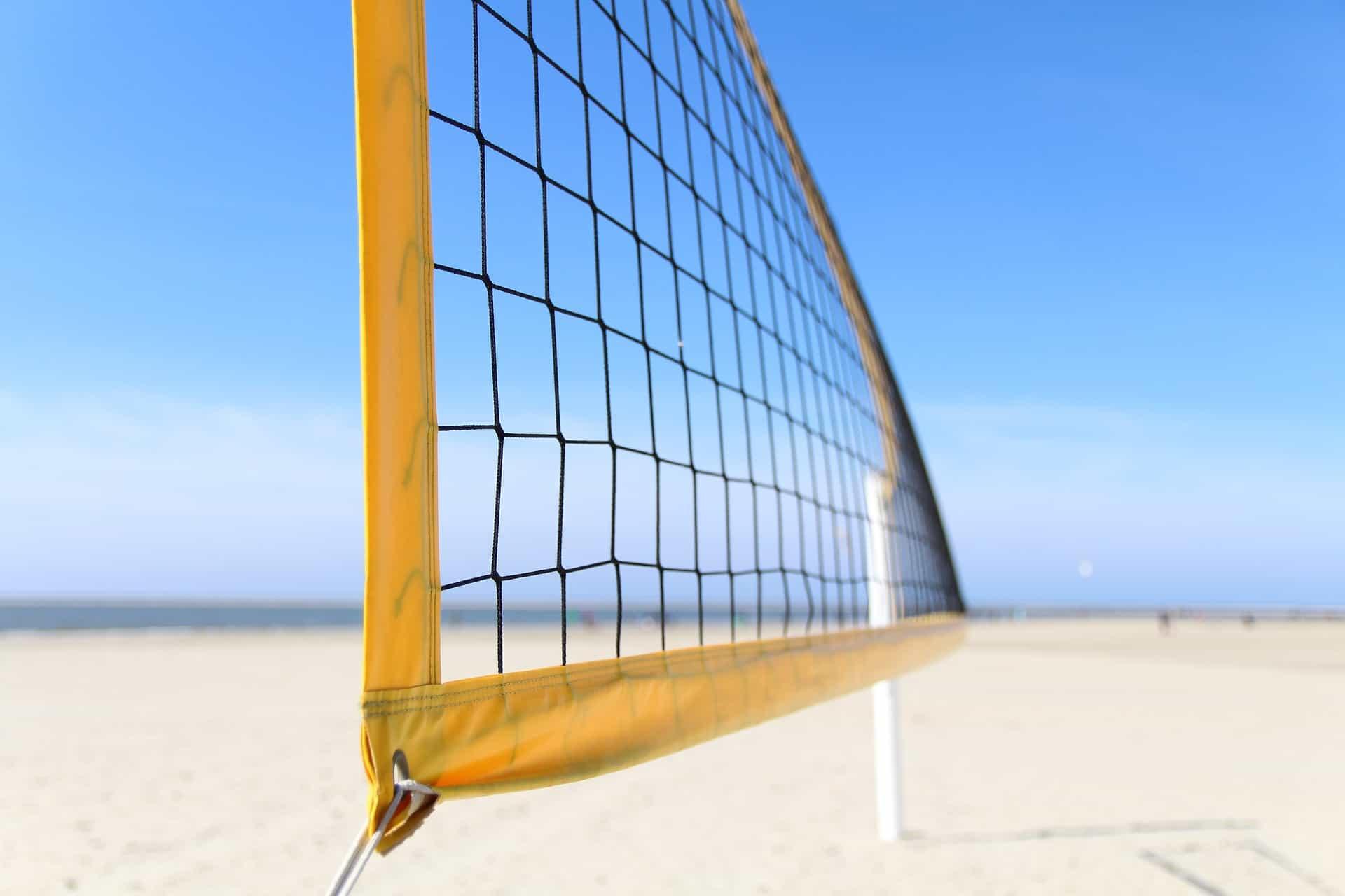 Beachvolleyballnetz am Strand mit blauem Himmel.