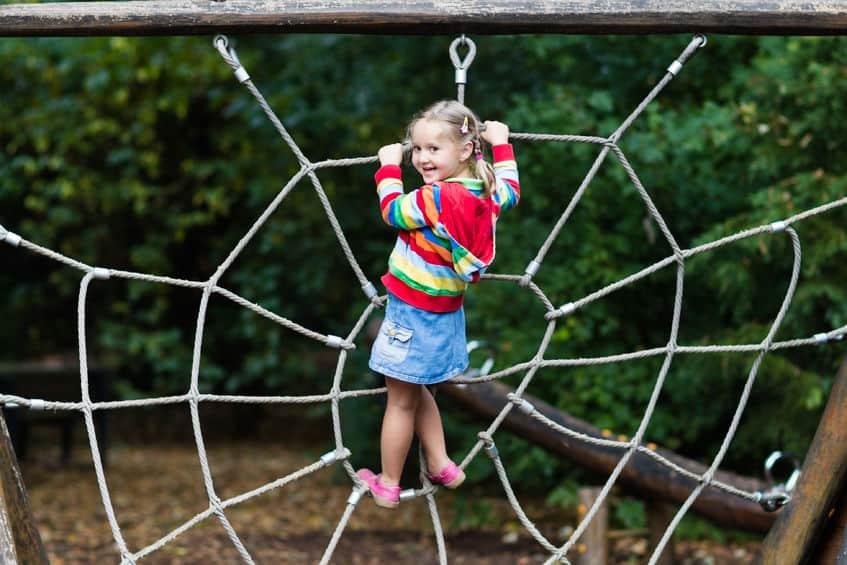 Kletternetz - Aktives Kleinkind beim Klettern im Kletternetz. Kinder spielen und klettern an sonnigen Sommertagen im Freien.